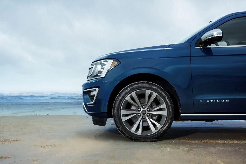 A blue Ford Expedition on a beach. Consumer Reports recommends buying a vehicle with pedestrian detection technology.