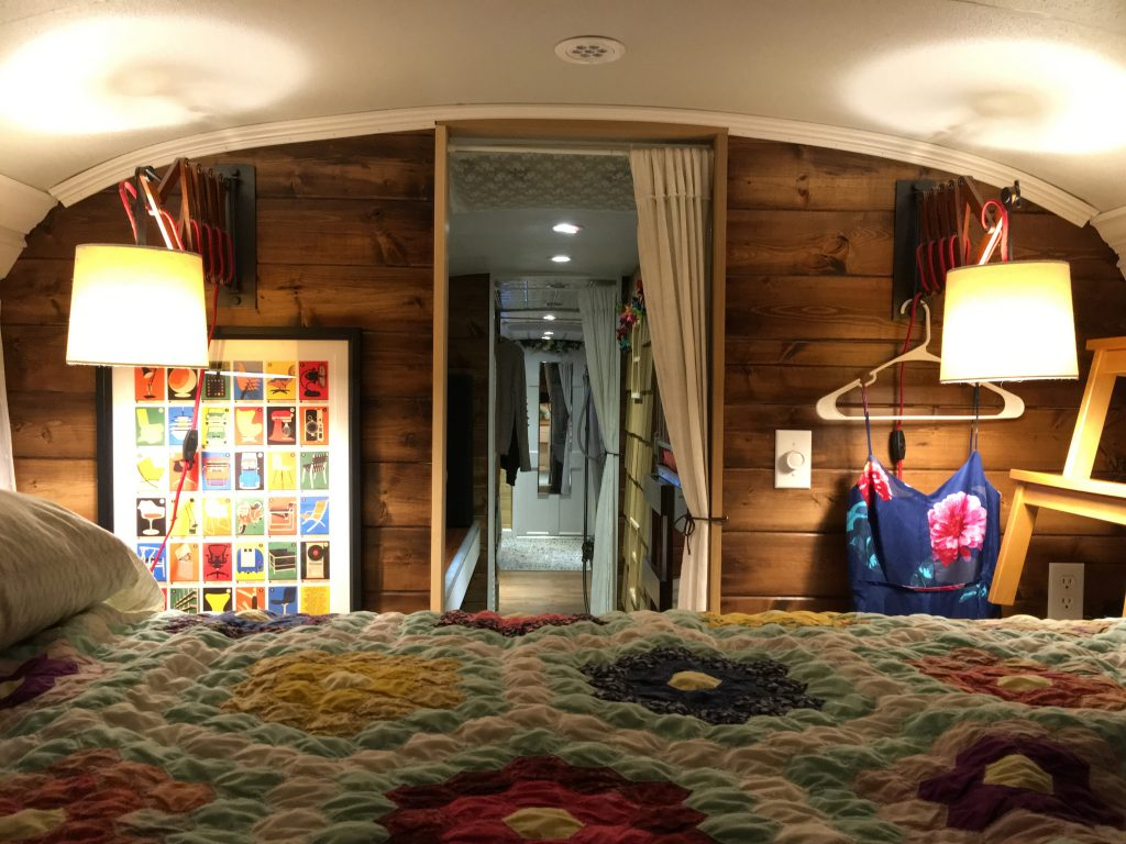 A homey bedroom built into the back of a school bus conversion