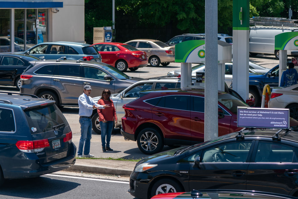 A line of cars waiting at the gas station. Gasoline is one of the yearly costs of ownership that can really add up, especially when fuel shortages increase gas prices.