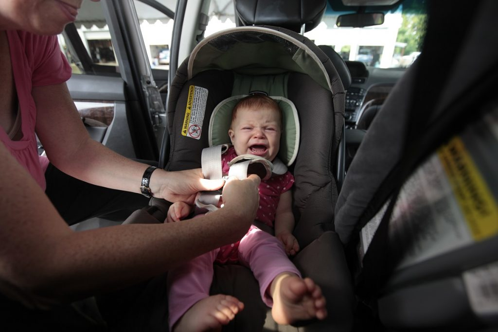 A crying baby strapped into a car seat.
