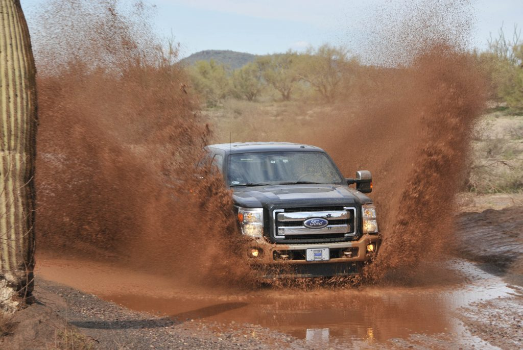 A diesel pickup truck splashes through a mud puddle