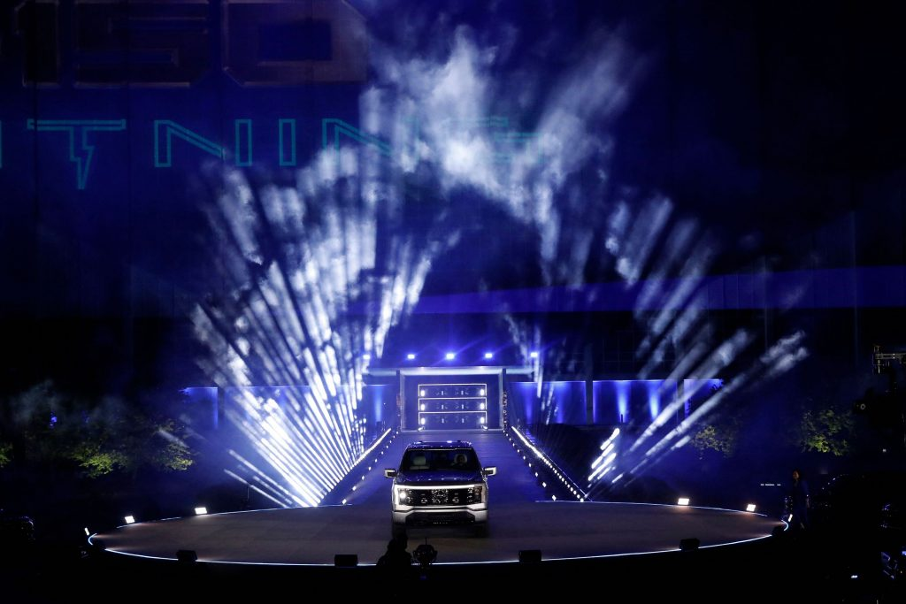 A silver Ford F-150 electric pickup truck on display in front of theatrical lighting