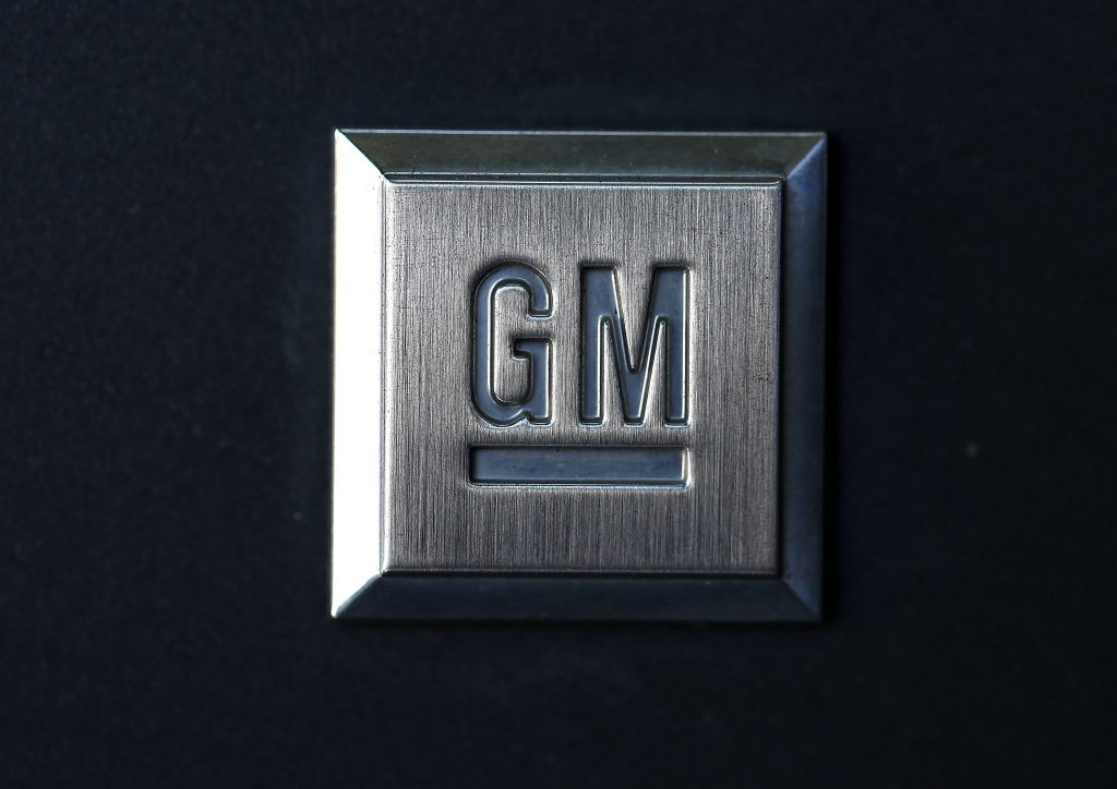 A General Motors logo stamped into a square metal plate