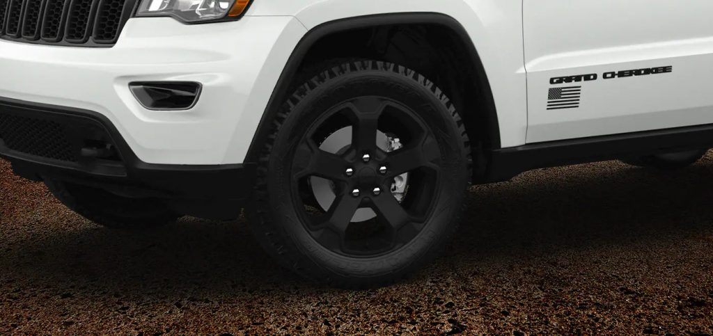 The black wheel of the white Jeep Grand Cherokee Freedom