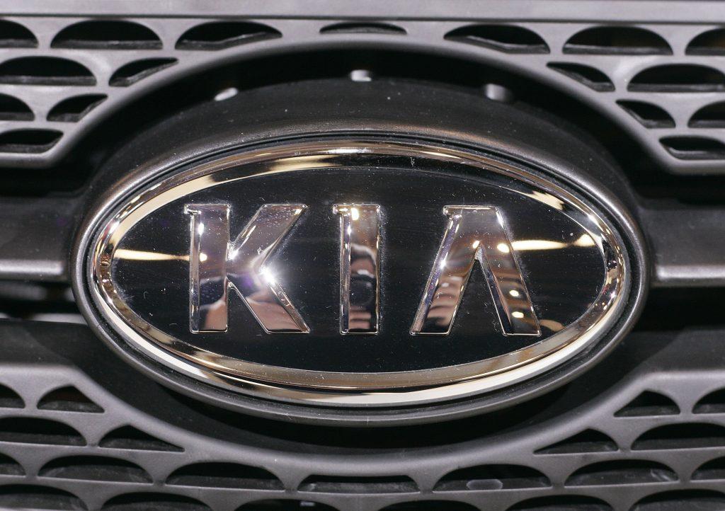 A chrome Kia emblem on a front grille
