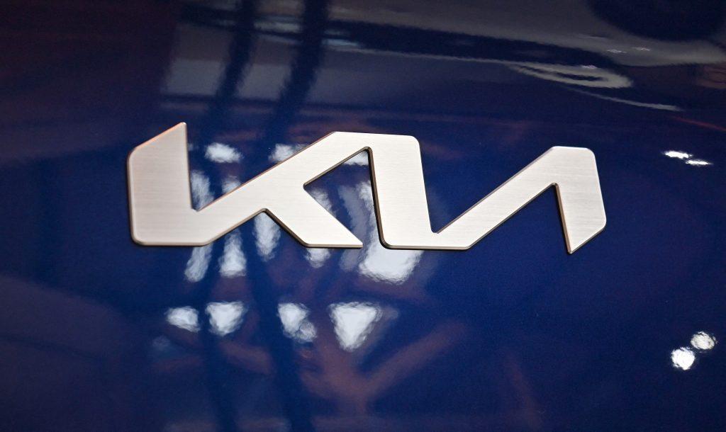 A silver Kia logo emblem on a blue EV6