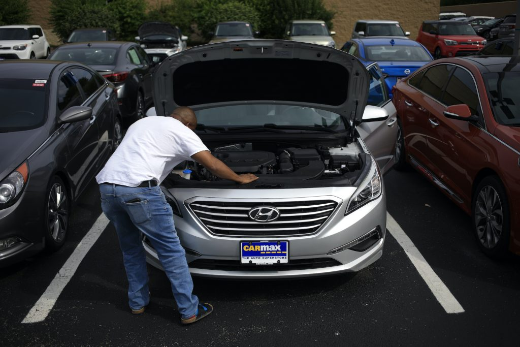 A customer inspects a pre-owned Hyundai while shopping for a used vehicle at a CarMax dealership.