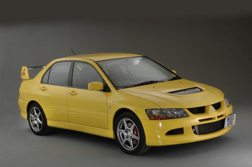 A yellow Mitsubishi Evolution sport sedan