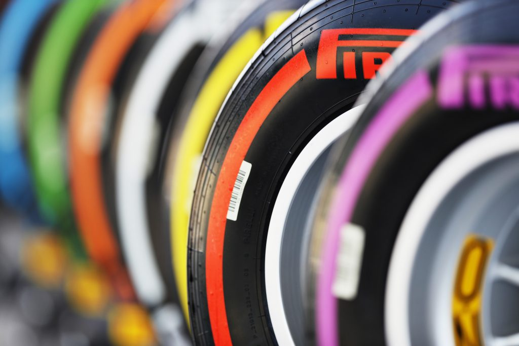 A row of Pirelli racing tires, each with a brightly colored stripe