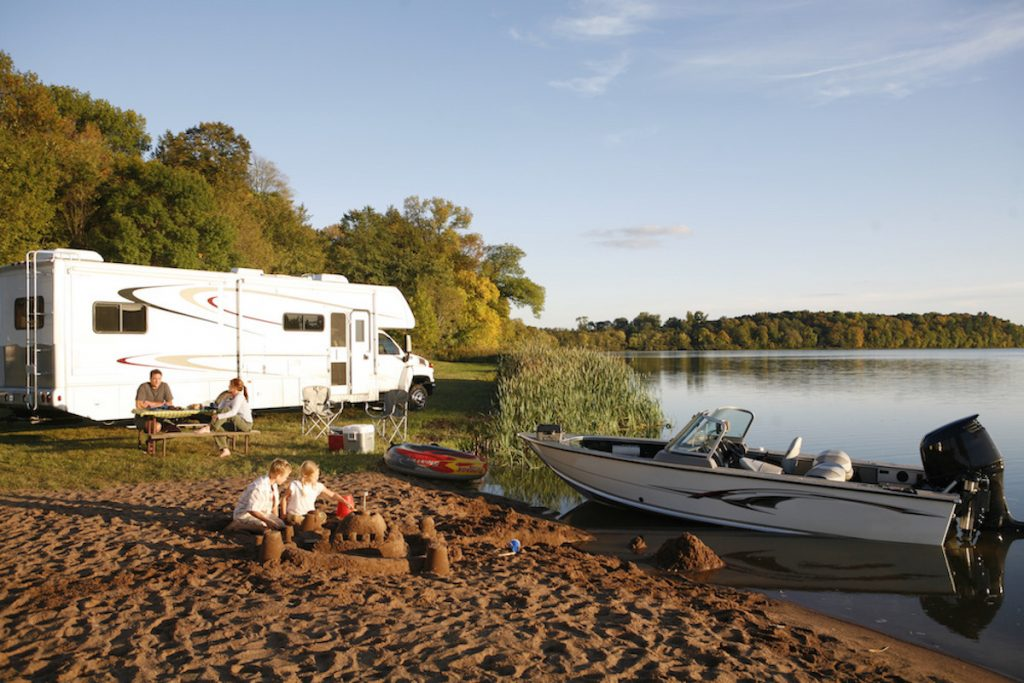 an RV camper and a small boat camping set up next to a lake