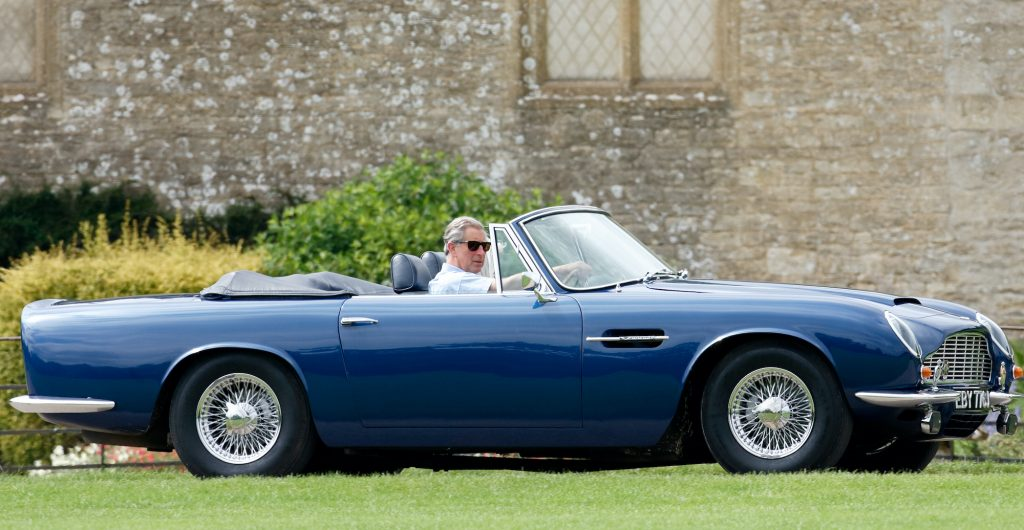 Prince Charles, Prince of Wales accompanied by Camilla, Duchess of Cornwall arrives, driving his 1969 Aston Martin DB6 Volante.