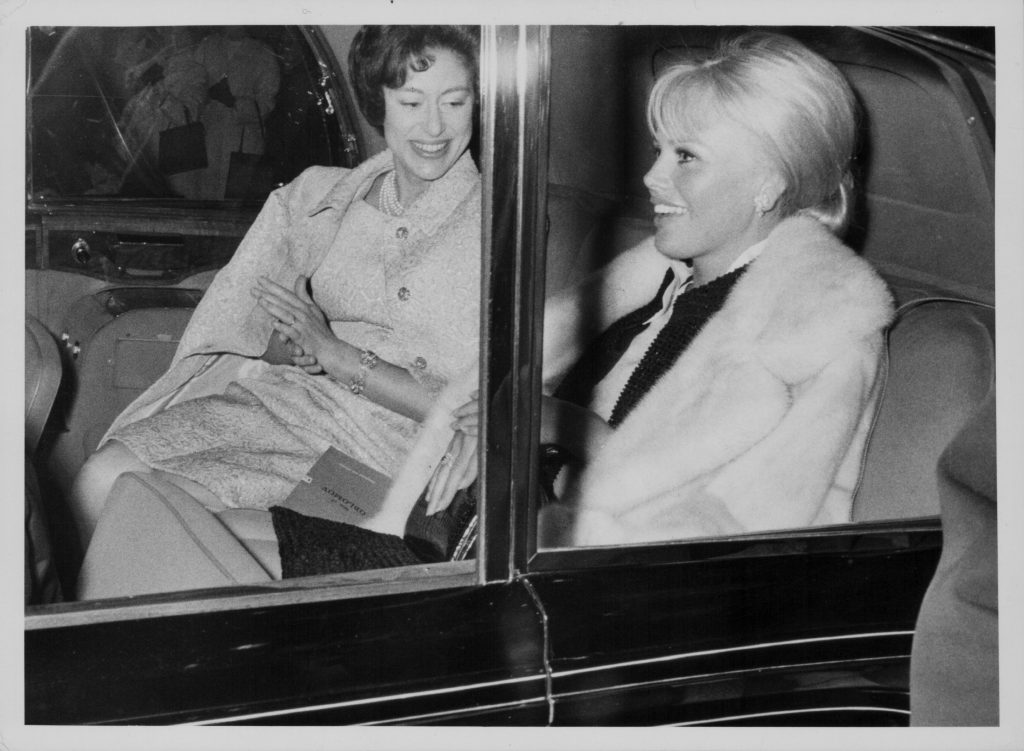 Princess Margaret and actor Britt Ekland in the back seat of a 1980 Rolls Royce Silver Wraith