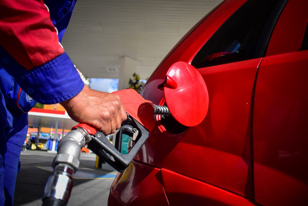 A man pumping gas into a red car