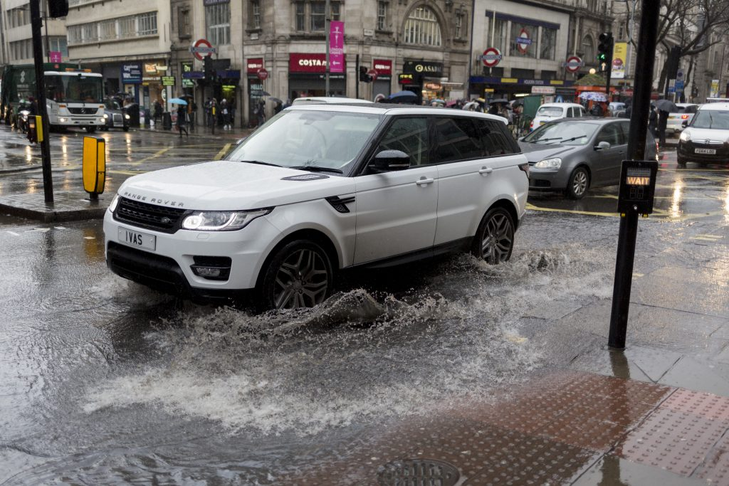 A range rover splashes through a storm puddle