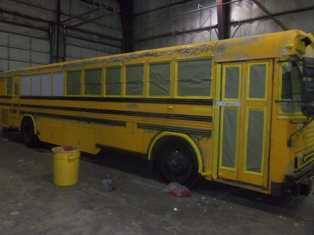 A school bus conversion prepped to be painted with tape and plastic sheeting