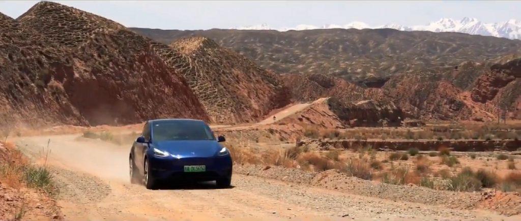 A dark blue Tesla drives through the mountains of China.