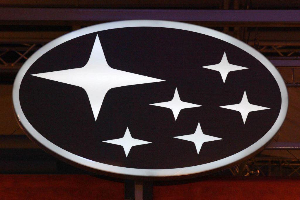 A white Subaru oval logo with 6 stars on a dark background