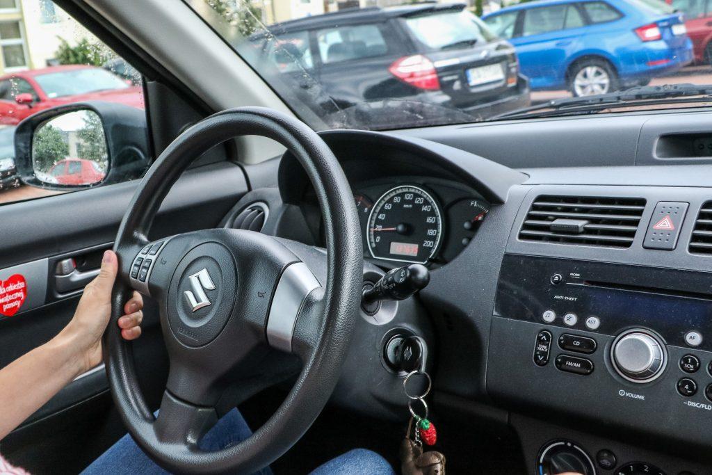 A woman driving her Suzuki Swift.