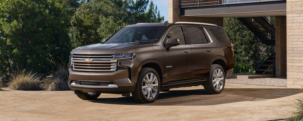 A brown 2021 Chevy Tahoe is parked outside of a house.