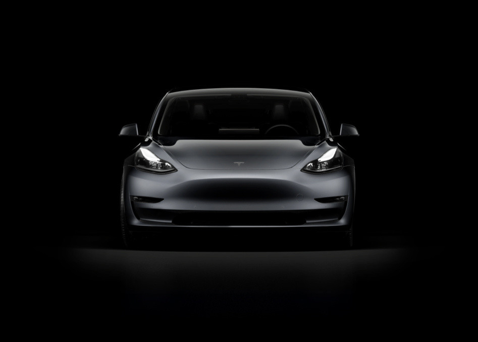 A dark gray Tesla Model 3 against a black background. The Tesla Model 3 police car is ready to be trialed in the U.K.