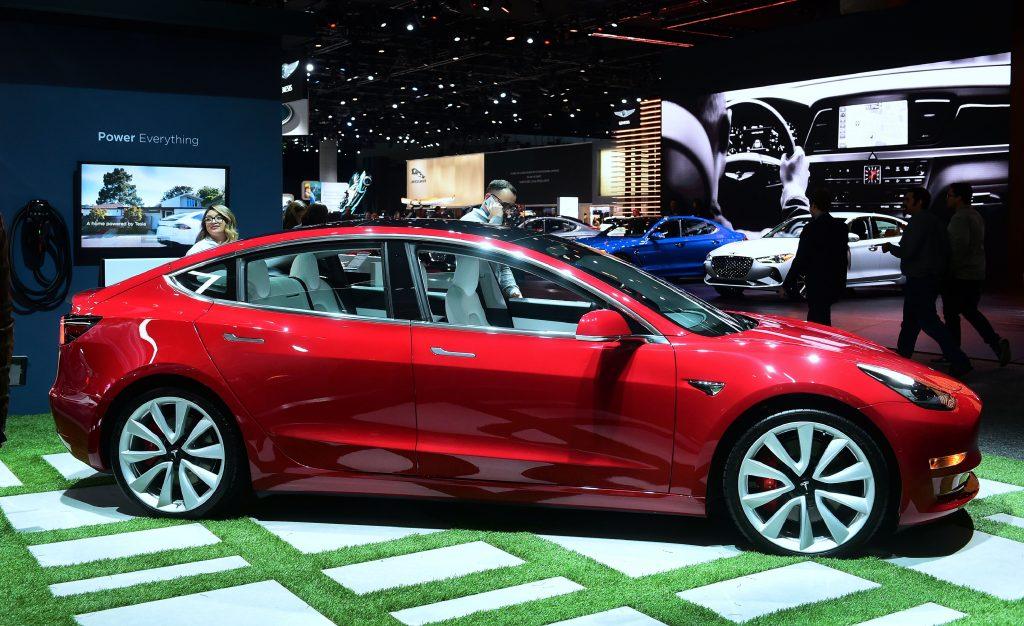 A red Tesla Model 3 EV on dispaly