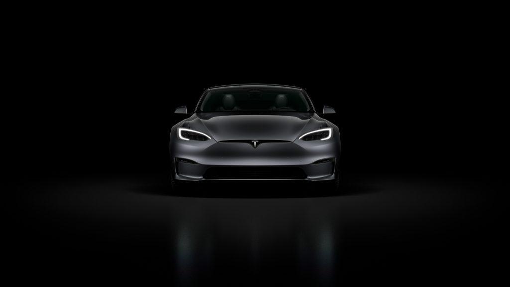 A black Tesla Model S Plaid in a black room