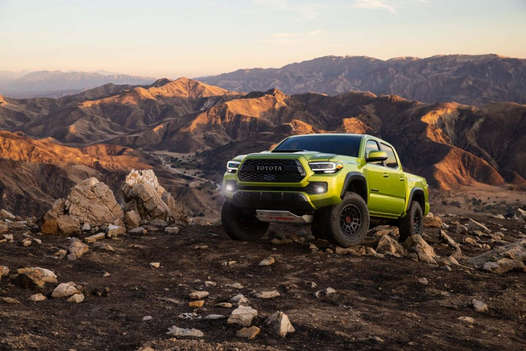 The 2022 Toyota Tacoma TRD Pro in Electric Lime climbing over rocks
