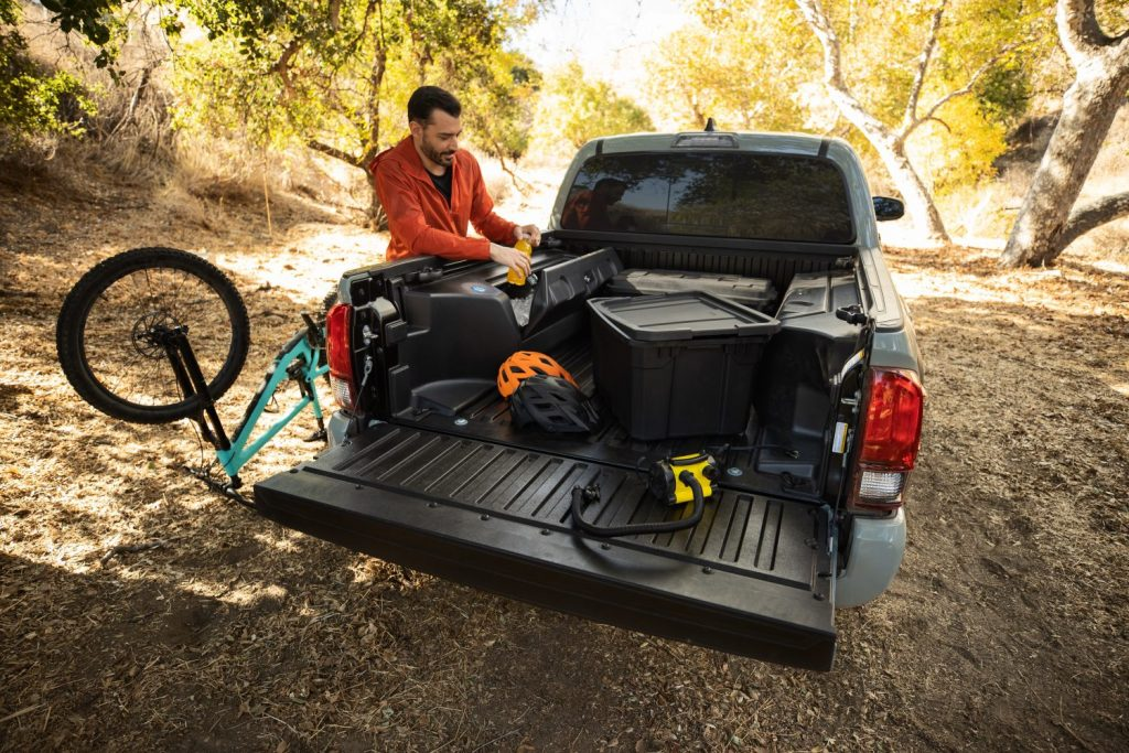 Bed view of the 2022 Toyota Tacoma Trail Edition off-road pickup truck at a campsite loaded with gear.