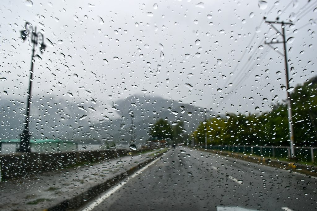 Car speckled with raindrops without windshield wipers
