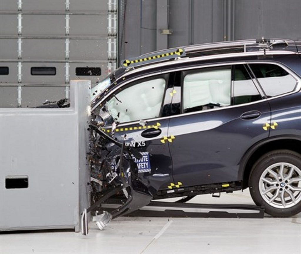A BMW X5 is being crash tested. The front of the car is smashed into a barrier.
