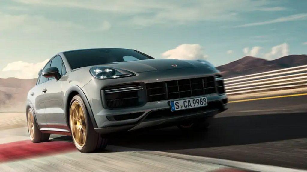 A silver 2021 Porsche Cayenne speeding with mountains in the background.