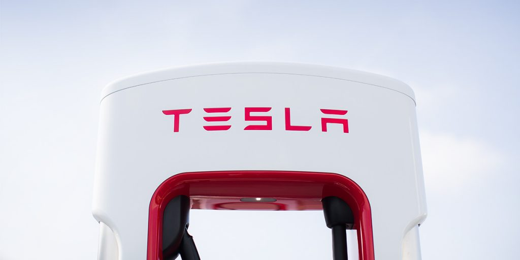 A Tesla Supercharger against a white sky.