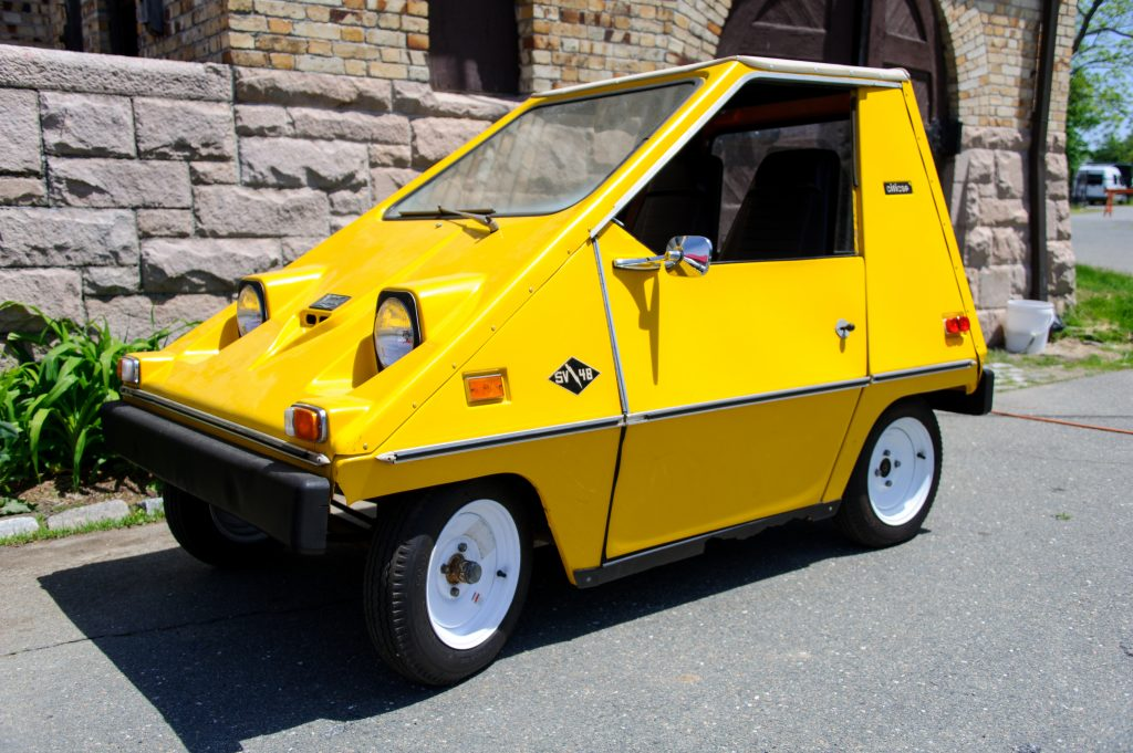 An electric Citicar SV48 parked next to a building