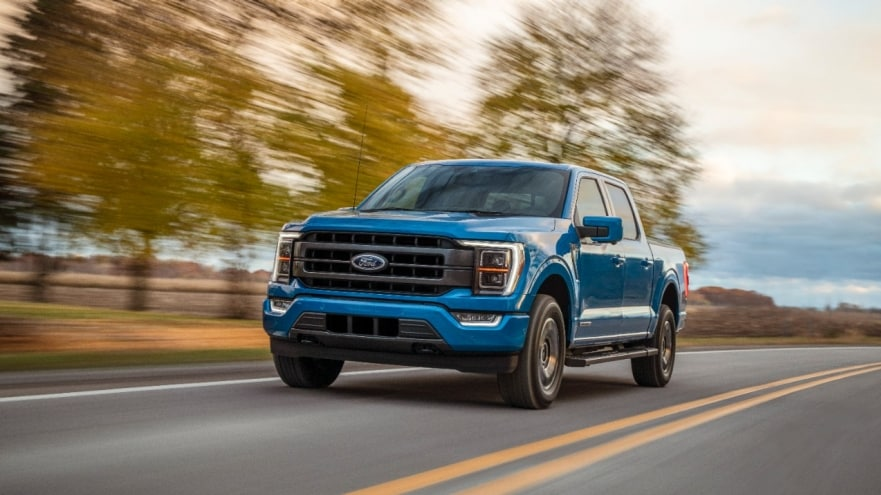 The 2021 Ford F-150 driving on the road by trees