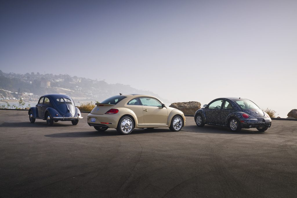 A blue 1949 Volkswagen Beetle, an off-white 2019 Beetle, and a blue printed 1998 New Beetle parked overlooking hills and an ocean