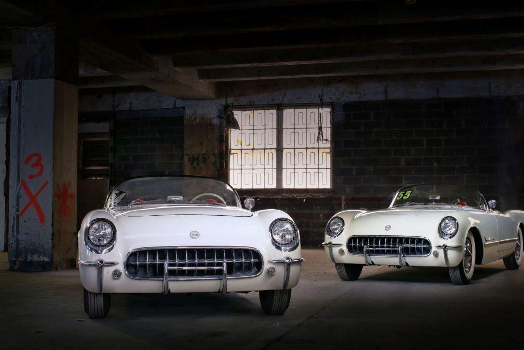 The white Lost 1954 Chevrolet Corvette next to the white Lost 1955 Chevrolet Corvette in a garage