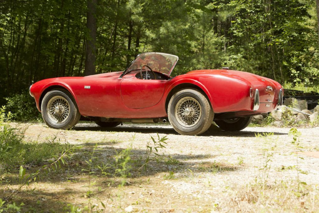 The side 3/4 view of a dusty red 1963 Shelby Cobra 260 parked by a forest