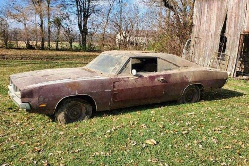 vintage dodge charger parked in the grass in need of some repairs