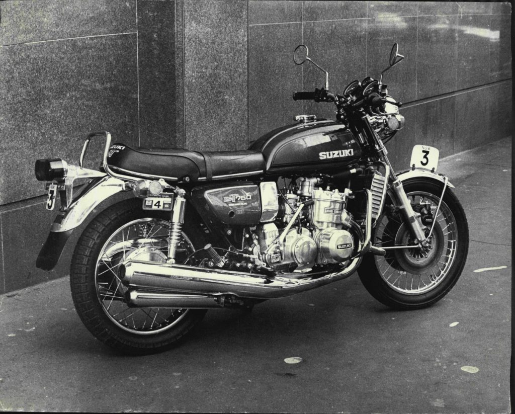 A black-and-white photo of a 1974 Suzuki GT750 in the city