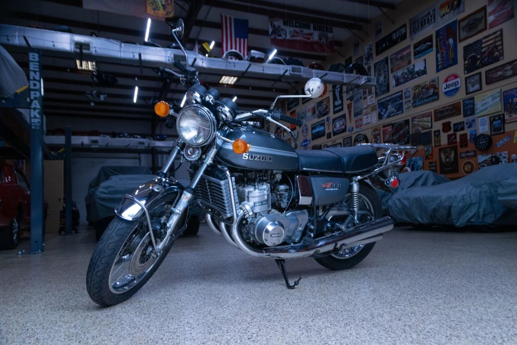 A gray-and-silver 1975 Suzuki GT750 in a garage with several covered cars