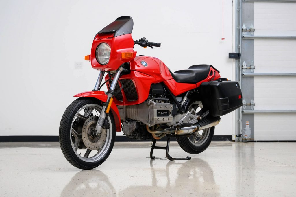 A red-and-black 1980 BMW K75 with black panniers in a garage
