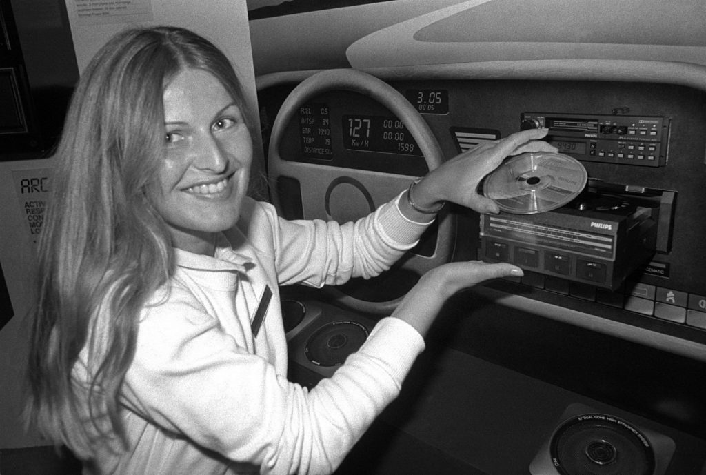 A black and white photo of a woman presenting a CD player in a vehicle