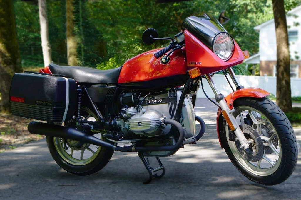An orange-and-black 1983 BMW R65LS with black panniers on a tree-lined driveway