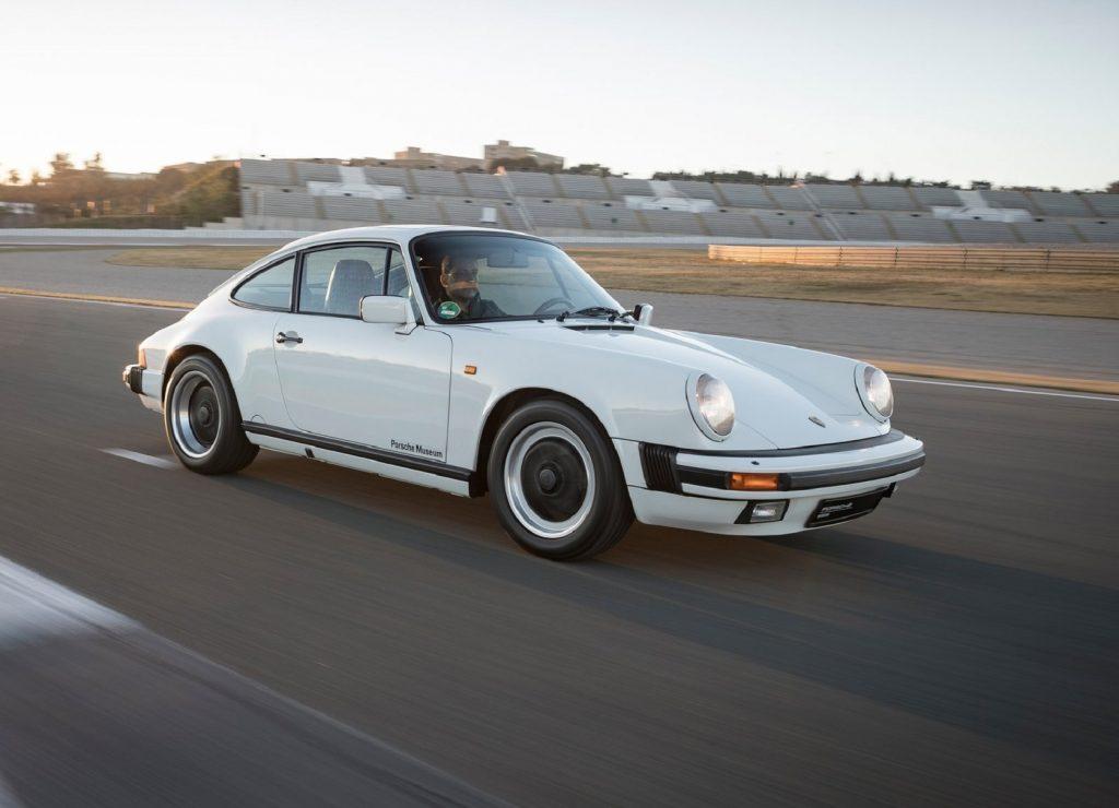 A white 1984 Porsche 911 Carrera 3.2 driving on a desert racetrack