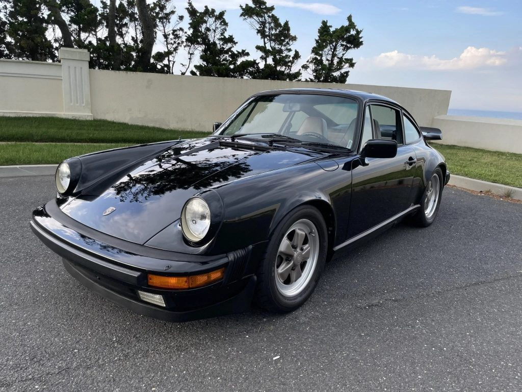 The front 3/4 view of a black 1984 Porsche 911 Carrera 3.2 parked in an oceanside parking lot