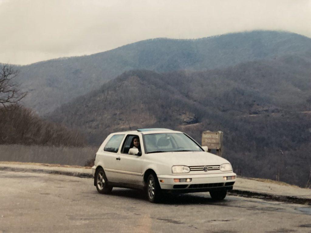 A 1995 Volkswagen Golf GTI model parked near grassy hills