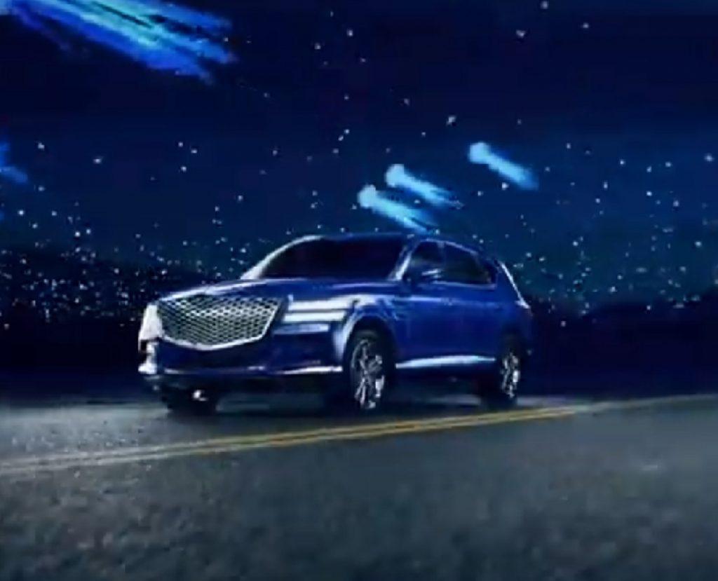 A blue 2021 Genesis GV80 against a dark night sky.