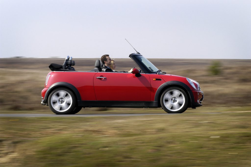 A red 2004 Mini Cooper convertible travels on a country road