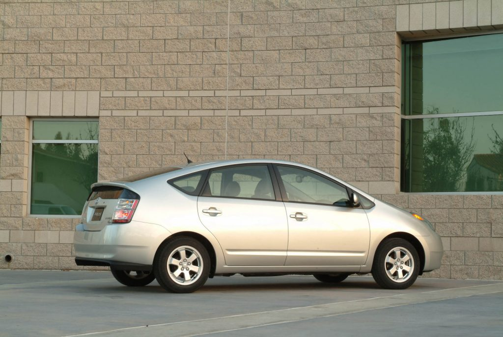 A silver 2004 Toyota Prius hybrid car parked next to a beige brick building