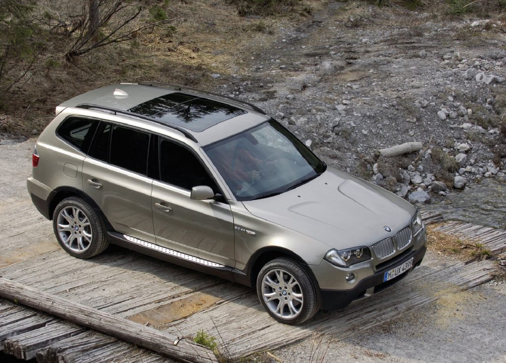 An overhead front 3/4 view of a tan 2007 BMW X3 3.0si crossing a wooden bridge over rocky ground